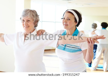 Portrait of sporty female supporting her friend while doing physical exercise in sport gym