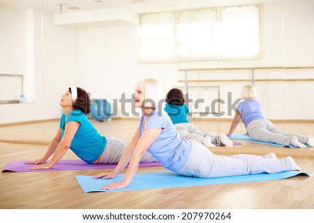 Portrait of sporty females doing stretching exercise in sport club - stock photo