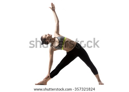 Portrait of sporty fit beautiful young brunette woman in sportswear bra and black pants working out, doing Utthita Trikonasana, Extended Triangle pose, studio full length, isolated, white background - stock photo