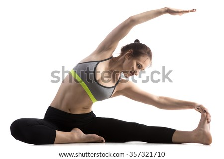 Portrait of sporty fit happy beautiful young woman in sportswear bra and black pants working out, doing Revolved Head to Knee pose, Parivritta Janu Sirsasana, studio full length, white background - stock photo