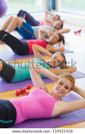 Portrait of sporty fitness class doing sit ups on exercise mats - stock photo