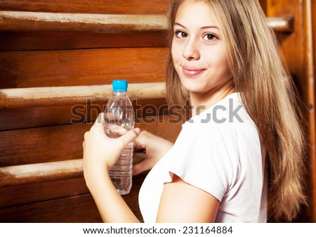 Portrait of sporty girl with bottle of water., girl taking a break at gymnastic training, on the wall bars in background. - stock photo