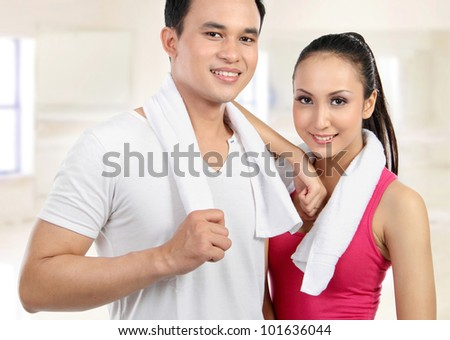 Portrait of sporty healthy young woman and man in the gym