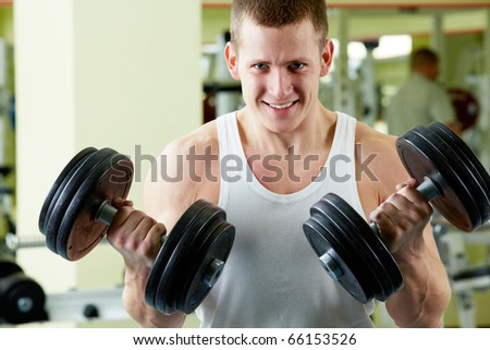 Portrait of sporty man with two dumbbells looking at camera - stock photo