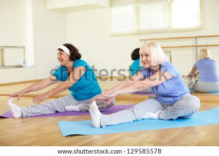 Portrait of sporty mature females doing stretching exercise in sport club - stock photo