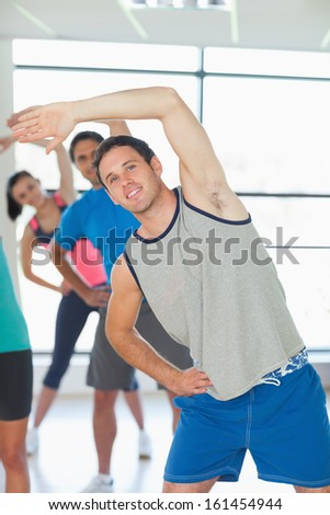 Portrait of sporty people doing power fitness exercise at yoga class - stock photo