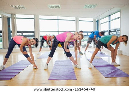 Portrait of sporty people stretching hands at yoga class in fitness studio - stock photo