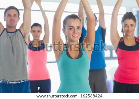Portrait of sporty people stretching up hands at yoga class in fitness studio