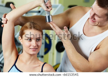 Portrait of sporty woman doing exercise with dumbbell and her trainer supporting - stock photo
