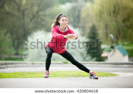 Portrait of sporty woman doing stretching exercises in park before training. Female athlete preparing for jogging outdoors. Runner doing side lunges. Sport active lifestyle concept. Full length - stock photo