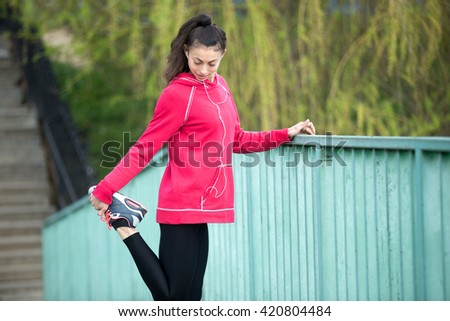 Portrait of sporty woman doing stretching exercises in park before training. Female athlete runner listening music while getting ready for running routine on the bridge. Sport active lifestyle concept - stock photo