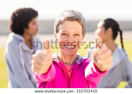 Portrait of sporty woman doing thumbs up in front of friends in parkland - stock photo
