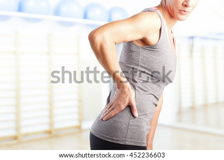 Portrait of sporty woman putting her hand on waist while has sport injury.
