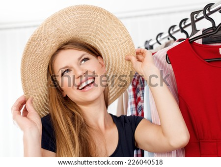 Portrait of spree shopping woman trying summer hat waiting for vacation. Young beautiful Caucasian woman model choosing accessories in retail shop.  - stock photo