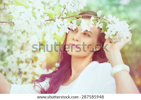 Portrait of spring brunette girl standing outdoor in blooming trees. Beautiful romantic woman in apple flowers. Young woman enjoying nature. - stock photo
