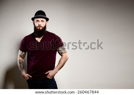 Portrait of standing handsome bearded man in hat - gray background - stock photo