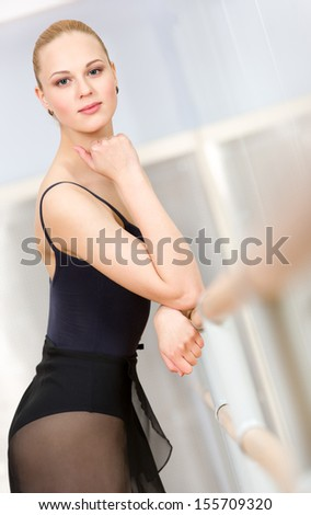 Portrait of standing near barre and mirrors ballerina wearing leotard and propping her head with hand - stock photo
