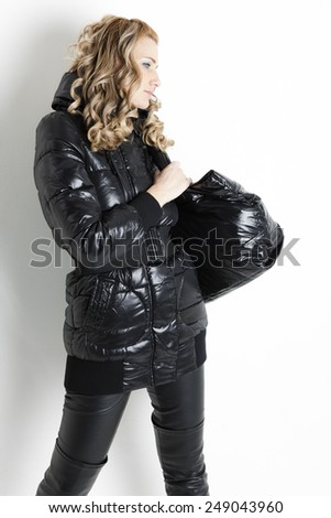 portrait of standing woman in black clothes with a handbag - stock photo