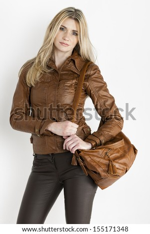 portrait of standing woman wearing brown clothes with a handbag - stock photo