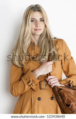 portrait of standing woman wearing brown coat with a handbag