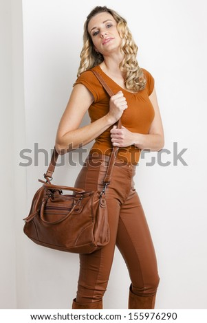 portrait of standing woman wearing fashionable brown clothes and boots with a handbag