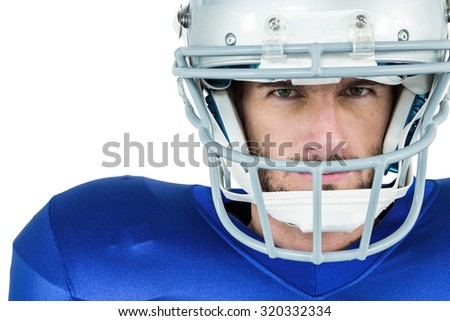 Portrait of stern American football player against white background - stock photo