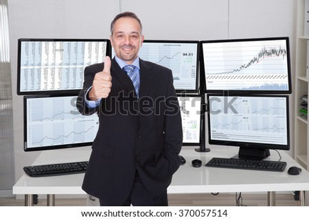 Portrait of stock market broker gesturing thumbs up against multiple monitors in office - stock photo