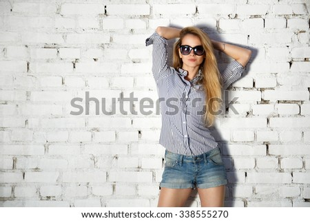 Portrait of Street Style Teen Girl with Hands behind Head on White Brick Wall Background. Trendy Fashion Casual Outfit.