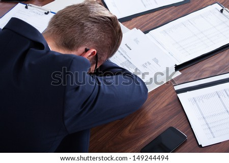 Portrait Of Stressed Businessman Sleeping In Office - stock photo