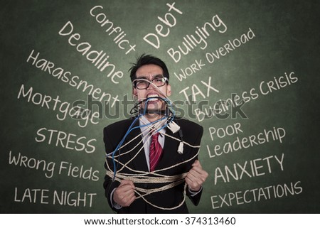 Portrait of stressed businessman tied with a rope in the classroom and doodles on the chalkboard - stock photo