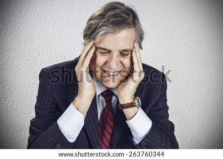 Portrait of stressed businessman with headache - stock photo