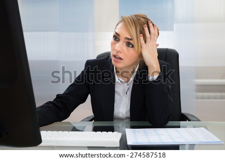 Portrait Of Stressed Businesswoman Working On Computer In Office - stock photo