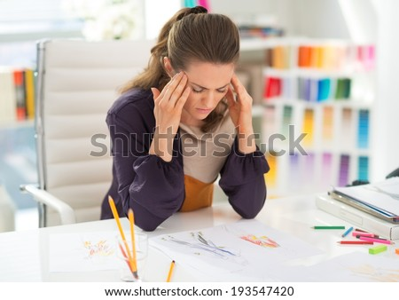 Portrait of stressed fashion designer in office - stock photo
