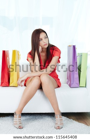 Portrait of stressed shopaholic sitting on sofa surrounded by paperbags