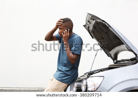 Portrait of stressed young man calling on cellphone for service his breakdown car - stock photo