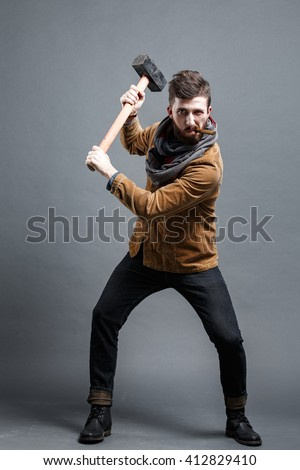 Portrait of strong black-haired man with hammer smoking cigar - stock photo