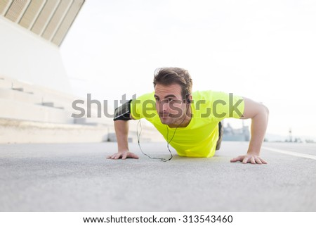 Portrait of strong build sports man with running armband doing pushes on asphalt city road and listening to music with headphones, young male jogger warm up before start his workout training outside - stock photo