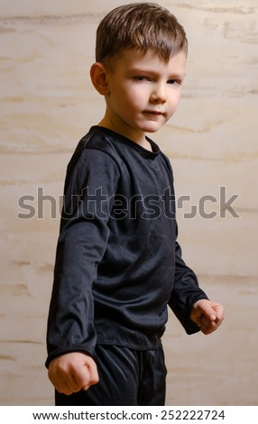 Portrait of Strong Serious Male Kid in Black Attire, Posing in Front Wooden Wall While Looking at the Camera. - stock photo
