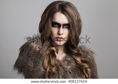 Portrait of strong woman in fur against grey background.