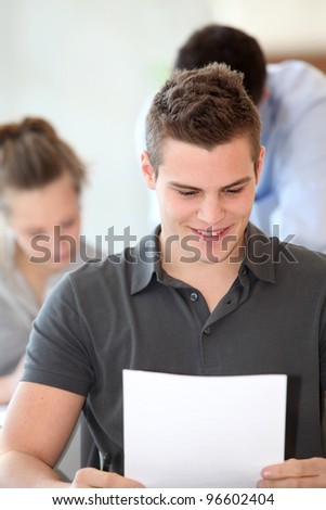 Portrait of student boy doing written exam - stock photo