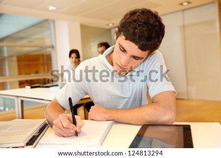 Portrait of student boy writing on notebook - stock photo