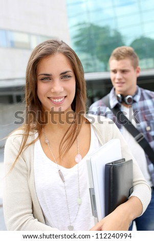 Portrait of student girl walking on university campus - stock photo