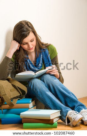 Portrait of student teenager girl reading a book
