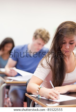 Portrait of students having a test in a classroom - stock photo