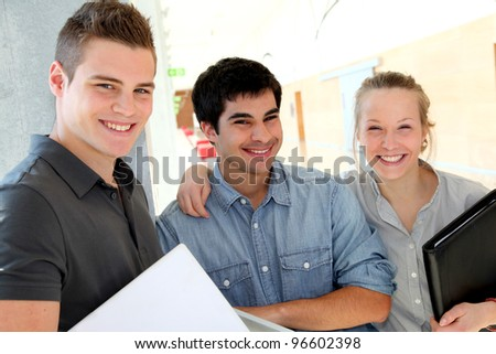 Portrait of students in school corridor - stock photo