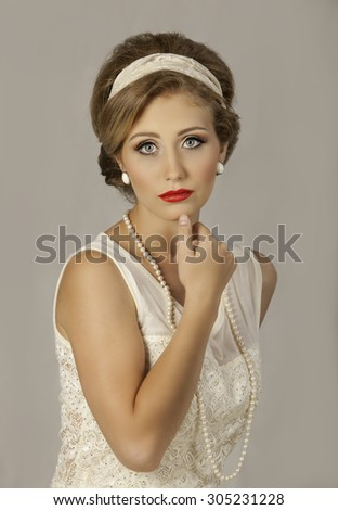 Portrait of stunning blonde fifties lady with pearl jewelry and red lipstick - stock photo