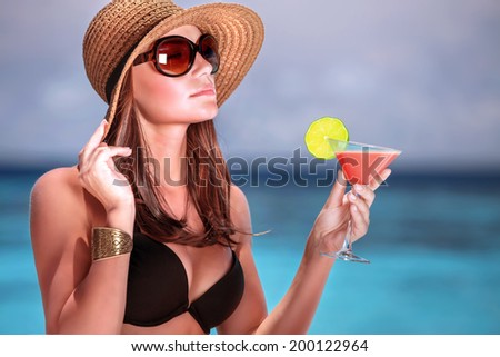 Portrait of stunning woman wearing stylish beach hat and sunglasses drinking cocktail outdoors, summer vacation on Maldives resort - stock photo