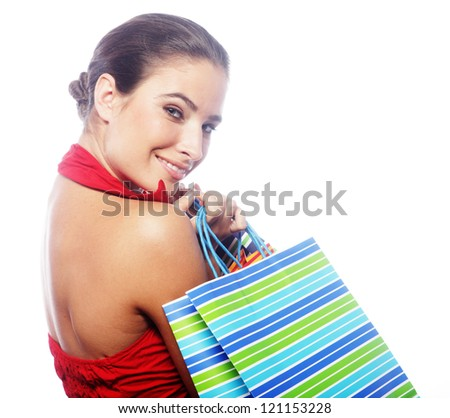 Portrait of stunning young woman carrying shopping bags against white background - stock photo