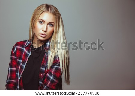 Portrait of stunning young woman wearing shirt looking at camera. Copyspace. - stock photo