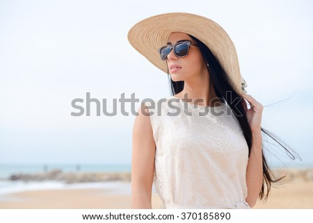 Portrait of stunningly beautiful young woman in a white dress and sunglasses. Gorgeous female on beach outdoors background - stock photo